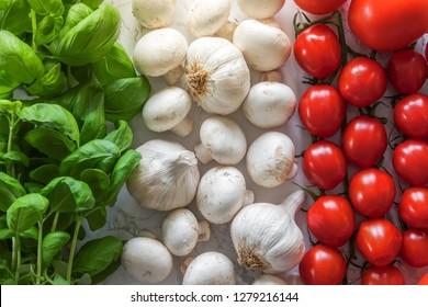 Italian flag made of ingredients for classic Italian food. Basil, mushrooms, garlic and tomatos.