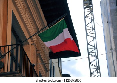 Italian flag on facade of the old building with crane for renovations.