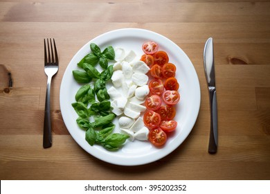 Italian flag on a plate: basil, mozzarella and cherry tomatoes