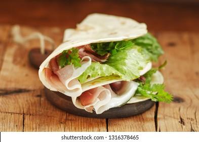 Italian flatbread called piadina with letucce salad, prosciutto crudo on wooden board.