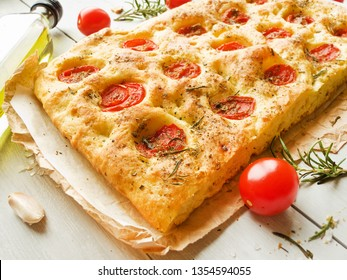 Italian focaccia bread with rosemary, garlic, cherry tomatoes and olive oil. Shallow dof.