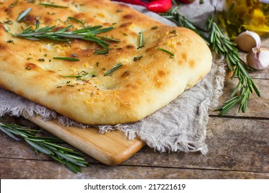 Italian focaccia bread with rosemary and garlic on a rustic background, selective focus