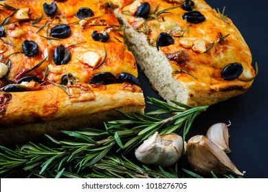 Italian focaccia with rosemary and olives on a black wooden table.