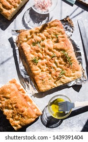 Italian focaccia, top view with pink salt and olive oil, top view composition, with direct strong light and directional shadow,over a light brown background