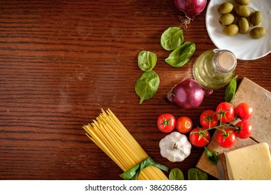 Italian food background with cherry tomatoes, cheese, olives, onion, olive oil, spaghetti, garlic - top view