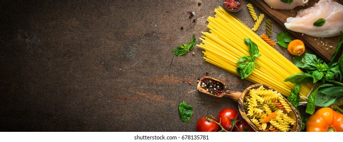 Italian food background. Pasta and meat. Uncooked Pasta tomato basil and chicken breast. Ingredients for cooking. Long banner format.