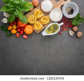 Italian food background, with tomatoes, basil, spaghetti, olives, parmesan, olive oil, garlic, peppercorns, parsley, chili and mushroom. Copy Space. From top view