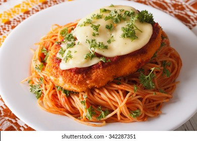 Italian food: Chicken Parmigiana and spaghetti close up on a plate on the table. horizontal