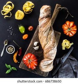 Italian food concept:  tagliatelle pasta, Beefsteak tomatoes, baguette and vegan recipe ingredients over stone table. Top view on vegan recipe ingredients. Mediterranean cuisine.