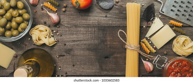 Italian food concept .Various kind of pasta with ingredients sweet basil ,tomato ,garlic ,parsley ,bay leaves ,pepper and parmesan cheese on wooden background flat lay.