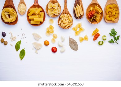 Italian food concept .Various kind of pasta with ingredients sweet basil ,tomato ,garlic ,parsley ,bay leaves ,pepper ,pine nut  and parmesan cheese on white wooden background flat lay and copy space.