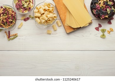 Italian food concept. Various kinds of colorful pasta in bowls. Top view on white wooden background. Copy space masterclass advertising