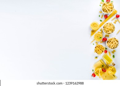 Italian food concept, various raw pasta assortment - spaghetti, lasagna, fusilli, tagliatelle, penne, tortellini, ravioli, with tomatoes and basil leaves white background copy space top view