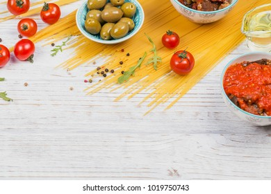Italian food cooking concept. Ingredients for preparation pasta spaghetti - tomato, olive oil, spices, herbs, green olives, tomato sauce, white wooden background. Top view with copy space for text