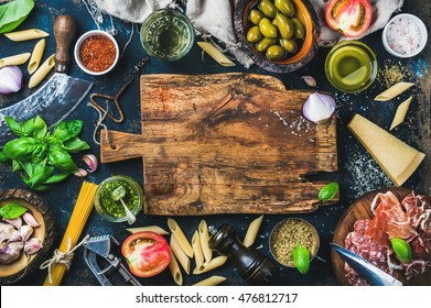 Italian food cooking ingredients on dark background with rustic wooden chopping board in center, top view, copy space