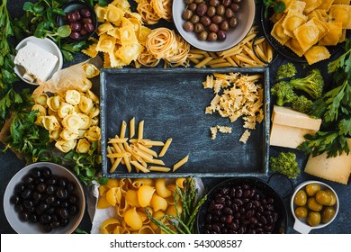 Italian food cooking ingredients with tagliatelle, penne, tortellini, ravioli, mafalda pasta and olives, green vegetables. Italian food health or vegetarian concept. Frame, top view with copy space.