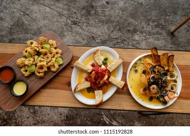 Italian food dishes viewed from above on white concrete background.