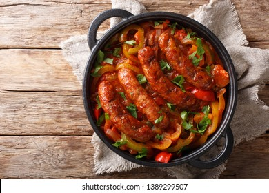 Italian food grilled sausage with grilled peppers, onions, herbs and tomatoes closeup in a frying pan on the table. horizontal top view from above