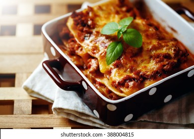 Italian Food. Hot Tasty Freshly Baked Lasagna Served with Basil Herb on Wooden Table. Close-up, Selective Focus.