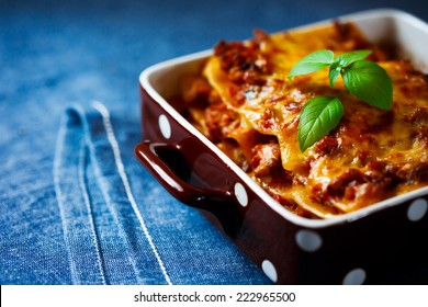 Italian Food. Hot tasty Lasagna plate served with fresh basil leaf. Close up view.