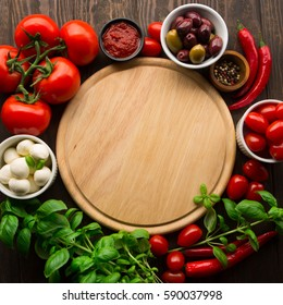 Italian food ingredients around empty cutting board on rustic wooden background, top view. National cuisine and cooking concept