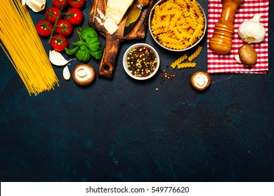 Italian food or ingredients background with fresh vegetables, pasta, cheese parmesan and spices. Top view, view from above. Copy space. Dark background.