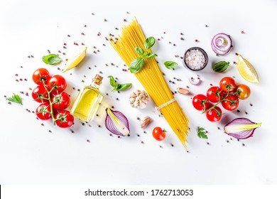 Italian food ingredients for  cooking Spaghetti Pasta. Raw spaghetti pasta with various ingredient - onion, tomatoes, garlic, basil, parsley, cheese, olive oil. On white table background