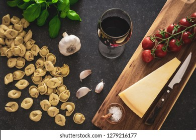 Italian food ingredients. A glass of red wine, tortellini pasta, cheese and herbs on dark stone background.