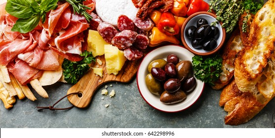 Italian food ingredients ham, salami, parmesan, olives, bread sticks