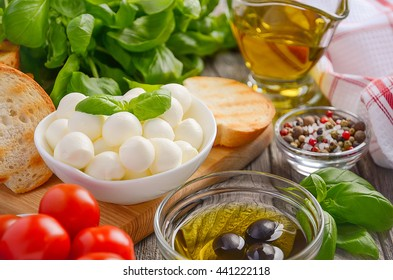 Italian food ingredients, mozzarella, tomatoes, basil and olive oil on rustic wooden background, selective focus