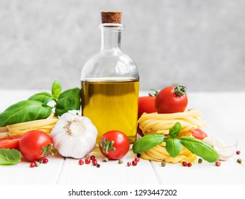 Italian food ingredients, olive oil, spices, pasta and tomatoes on a white wooden table