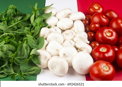 Italian food ingredients on Italian flag, basil on green, mushrooms and garlic on white and tomatoes on red.