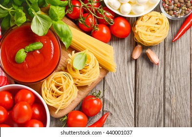 Italian food ingredients on rustic wooden background, top view, copy space