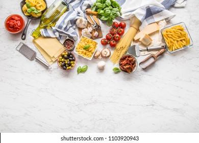 Italian food ingredients pasta olive oil parmesan cheese basil garlic mushrooms tomatoes olives on marble board.