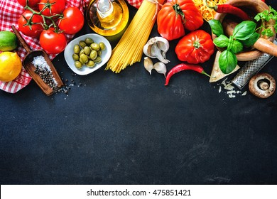 Italian food ingredients. Vegetables, olive oil, herbs, cheese and pasta on dark background