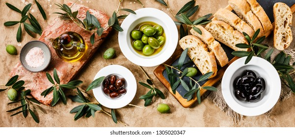 Italian food with Olives, Sliced bread Ciabatta and Olive Oil on travertine background copy space