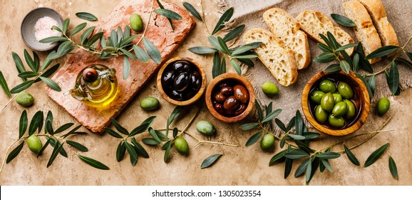 Italian food with Olives, Sliced bread Ciabatta and Olive Oil on travertine background