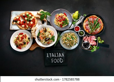 Italian food  on dark background with pasta, pizza, top view, copy space