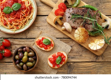 Italian food pizza pasta and beef steack on rustic kitchen table
