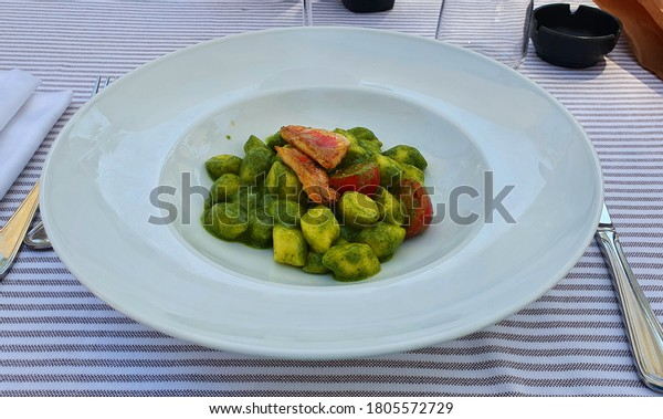 Italian food: potato gnocchi with pesto sauce and triglia.
