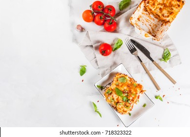 Italian food recipe. Dinner with classic lasagna Bolognese with Bechamel sauce, Parmesan cheese, basil and tomatoes, on white marble table, copy space
