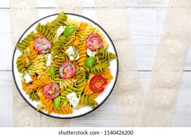Italian food - Salad with colorful pasta, cherry tomatoes, feta cheese and fresh basil on white wooden background