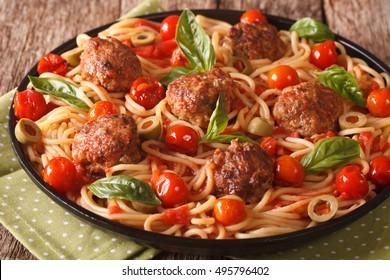 Italian food: spaghetti with meatballs, olives, basil and tomato sauce closeup on a plate. horizontal