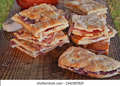 Italian food: traditional flat bread called focaccia or schiacciata, a flat oven-baked bread product with olive oil or lard of pork, sandwich very popular in Italy filled with ham or pork sausage
