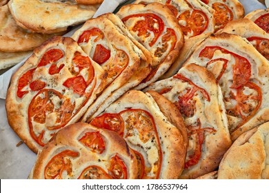 Italian food: traditional focaccia, schiacciata of Tuscany, a flat oven-baked bread product with olive oil and tomato, very popular in Italy. Similar to pizza doughs but more soft and thick