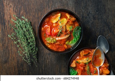 Italian food. Two bowl of soup minestrone with seasonal vegetables on wooden table, top view