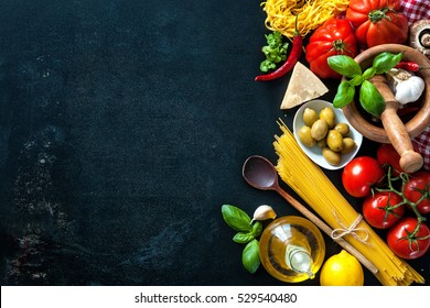 Italian food. Vegetables, olive oil, herbs and pasta on dark background