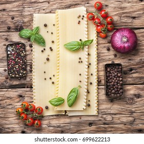 Italian food.Preparing Italian lasagne with basil on wooden background