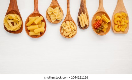 Italian foods concept and menu design. Various kind of Pasta Farfalle, Pasta A Riso, Orecchiette Pugliesi, Gnocco Sardo and Farfalle in wooden spoons setup on white wooden background with flat lay.