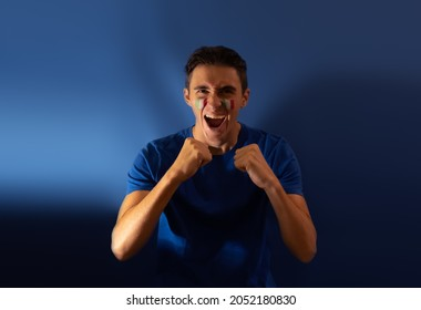 italian football fan shouting for his national team, isolated on blue background. Flag painted over face